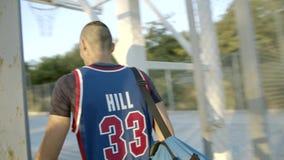 Баскетболист приходит к спортивной площадке для игры Баскетболист играет на рассвете солнца E сток-видео