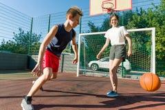 Баскетбольный матч Streetball с 2 игроками, подростками девушкой и мальчиками, утром на баскетбольной площадке стоковое фото