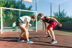 Баскетбольный матч Streetball с 2 игроками, подростками девушкой и мальчиками, утром на баскетбольной площадке стоковые фото