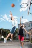 Баскетболисты играя баскетбол совместно на суде Стоковое Изображение RF