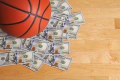 Баскетбол на куче 100 долларовых банкнот Стоковая Фотография RF