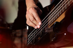 Басовая гитара в руках музыканта Стоковое Изображение
