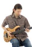 Басовый гитарист сконцентрированный на его басовой гитаре стоковое фото rf