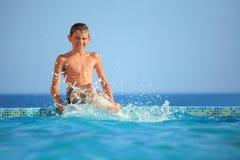 бассеин ног мальчика брызгает воду подростка Стоковая Фотография