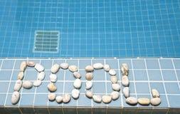 ` Бассейна ` надписи положено вне камешком на сторону бассейна стоковая фотография
