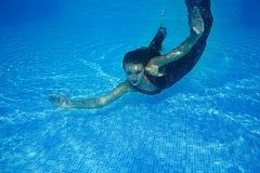 Бассейн солнечного дня красивого заплыва подныривания платья девушки женщины подводного голубой Стоковые Изображения RF