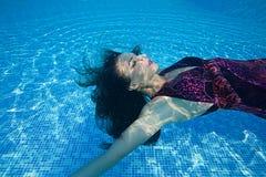 Бассейн солнечного дня красивого заплыва подныривания платья девушки женщины подводного голубой Стоковая Фотография