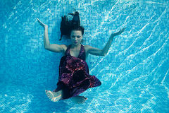 Бассейн солнечного дня красивого заплыва подныривания платья девушки женщины подводного голубой Стоковые Фото
