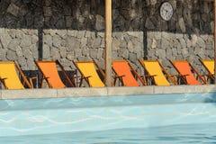 Бассейн с оранжевыми и желтыми sunbeds Стоковое фото RF