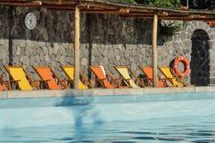 Бассейн с оранжевыми и желтыми sunbeds Стоковые Фото