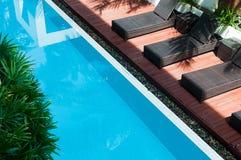 Бассейн с темными стульями рядом с Стоковое Фото