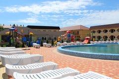 Бассейн с loungers солнца на территории туристического комплекса Стоковое фото RF
