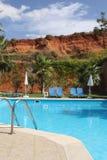 Бассейн с sunbeds и зонтиками солнца Стоковое Фото