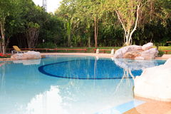 Бассейн, loungers солнца рядом с садом и здания Стоковая Фотография RF
