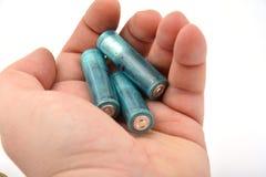 3 батареи AAA в руке изолированной на белизне Стоковые Изображения RF