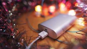 Батарея серебряного powerbank внешняя для быстрого поручая ПК smartphone или таблетки лежа на таблице окруженный путем проблескив акции видеоматериалы