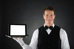 Батлер держа поднос с таблеткой цифров Стоковое Изображение