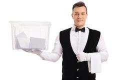 Батлер держа урну для избирательных бюллетеней заполненный с голосованиями стоковая фотография