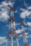 Башни передачи против голубого неба и облаков Стоковая Фотография