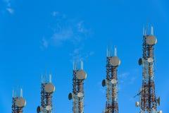 Башни радиосвязи аранжированные как диаграмма в виде вертикальных полос на ясной сини Стоковое Фото
