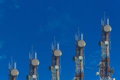 Башни радиосвязи аранжированные как диаграмма в виде вертикальных полос на ясной сини Стоковая Фотография RF