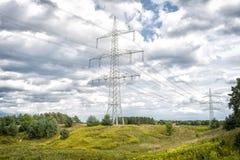 Башни силы на естественном ландшафте Башни передачи на облачном небе Структура опоры электричества с линиями электропередач высок Стоковое Изображение