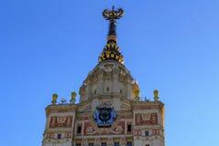 Башня государственного университета MSU Lomonosov Москвы с гербом страны СССР и звезды на крупном плане шпиля на backgrou голубог Стоковые Изображения
