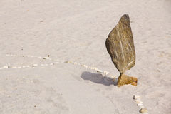 Башня Дзэн каменная на пляже, с выплеском волны моря вокруг Вытянутые камни в балансе на seashore Стоковое Изображение RF