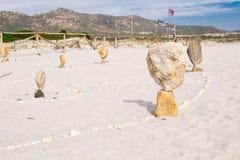 Башня Дзэн каменная на пляже, с выплеском волны моря вокруг Вытянутые камни в балансе на seashore Стоковые Изображения