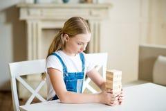 Башня здания девушки Preteen от деревянных кирпичей на таблице Стоковая Фотография RF