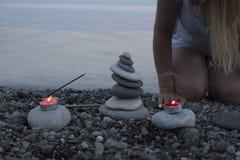 Башня камешка моря на пляже на заходе солнца, с свечами закрывает вверх Стоковое фото RF