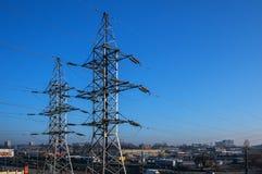 Башня линий высокого напряжения на фоне промышленной городской местности и голубого неба Стоковая Фотография RF