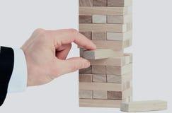 Башня от деревянных блоков и руки ` s человека принимает один блок Стоковое фото RF