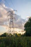 Башня передачи энергии на растительности предпосылки на вечере лета Стоковое Изображение