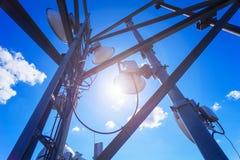 Башня радиосвязи с микроволной, антеннами радио и спутниковыми антенна-тарелками с тенями на крыше против голубого неба и солнца Стоковое Фото