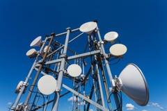 Башня радиосвязи с антеннами микроволны и спутниковые антенна-тарелки с кабелями и оптическим волокном Стоковые Фотографии RF