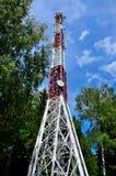 Башня радиосвязи с клетчатыми и спутниковыми антеннами против голубого неба и леса стоковые фотографии rf