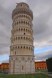 Башня склонности Пизы против пасмурной драматической предпосылки неба Стоковое Изображение