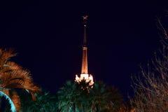 Башня со шпилем загоренным фарами вечером стоковое изображение