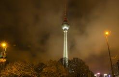 Башня ТВ Берлина положенная в кожух в облака на ноче, Германию Стоковые Фото