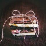 Башня шоколадных батончиков обернутых как настоящий момент шоколада Различные части шоколада над темной деревянной предпосылкой Стоковые Изображения