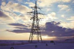 Башня электричества на вечере заволакивает предпосылка на зиму Стоковая Фотография