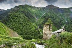 Башня Svan старая в горном селе в зоне Svaneti Georgia Горы покрыли зеленую траву Грузинская природа Стоковое фото RF
