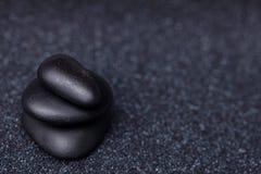 Балансируя мирные черные камни в расслабляющем Дзэн садовничают Стоковая Фотография RF