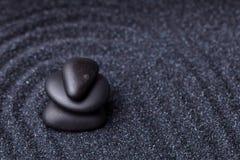 Балансируя черные камни массажа в расслабляющем Дзэн садовничают Стоковые Изображения RF