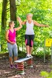 Балансы женщины получая помощь от беременного партнера тренировки Стоковые Изображения RF