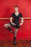 Балерина выполняя против красной стены в студии Стоковая Фотография RF