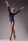 Балерина в голубом обмундировании представляя на пальцах ноги, студии сняла руки вверх Стоковые Изображения RF