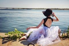 Балерина в шляпе сидя на речном береге Стоковые Фото