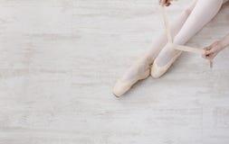 Балерина кладет дальше ботинки балета pointe, грациозно ноги Стоковые Фотографии RF